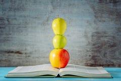 Ανοικτά βιβλίο και μήλα που συσσωρεύονται μπροστά από το ξύλινο υπόβαθρο στοκ εικόνες με δικαίωμα ελεύθερης χρήσης