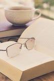 Ανοικτά βιβλίο και γυαλιά σε έναν ξύλινο πίνακα Στοκ Εικόνα