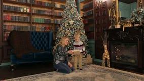 Ανοικτά δώρα μητέρων και παιδιών κοντά στο χριστουγεννιάτικο δέντρο απόθεμα βίντεο