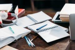 Ανοικτά κενά σημειωματάρια με τις μάνδρες και βιβλία στον ξύλινο πίνακα Στοκ εικόνα με δικαίωμα ελεύθερης χρήσης