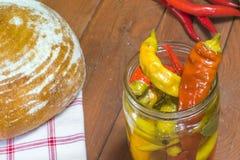 Ανοικτά παστωμένα πιπέρια τσίλι στο βάζο γυαλιού με το ψωμί και το φρέσκο CH Στοκ Φωτογραφία