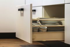 Ανοικτά συρτάρια κουζινών με τα πιάτα και τα πιάτα φλυτζανιών Στοκ φωτογραφίες με δικαίωμα ελεύθερης χρήσης