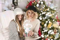Ανοικτά χριστουγεννιάτικα δώρα κοριτσιών κοντά στο χριστουγεννιάτικο δέντρο Στοκ Φωτογραφίες