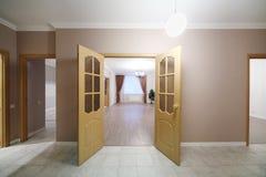Ανοικτές ξύλινες πόρτες που οδηγούν στο ευρύχωρο δωμάτιο Στοκ εικόνες με δικαίωμα ελεύθερης χρήσης