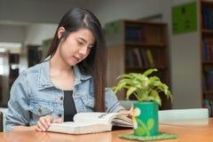 Ανοικτή ανάγνωση βιβλίων σπουδαστών αυτό στην πανεπιστημιακή βιβλιοθήκη Στοκ φωτογραφία με δικαίωμα ελεύθερης χρήσης