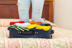 Ανοικτή βαλίτσα με τα ενδύματα μέσα να βρεθεί στο κρεβάτι, πόδια της γυναίκας στο υπόβαθρο, έννοια φιλοξενουμένων ξενώνων Στοκ Εικόνες