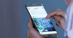 Ανοικτή εφαρμογή Instagram χεριών στο smartphone φιλμ μικρού μήκους