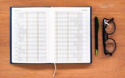 Ανοικτή ημερολογιακή σελίδα βιβλίων αρμόδιων για το σχεδιασμό ημερολογίων με τα γυαλιά και μάνδρα στο θόριο Στοκ Εικόνες