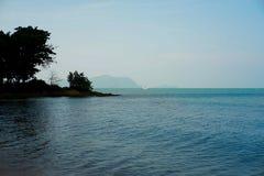 Ανοικτή θάλασσα με τα κύματα και τους βράχους και τους λόφους και τα δέντρα Στοκ εικόνες με δικαίωμα ελεύθερης χρήσης