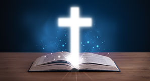 Ανοικτή ιερή Βίβλος με τον καμμένος σταυρό στη μέση Στοκ Εικόνες