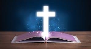 Ανοικτή ιερή Βίβλος με τον καμμένος σταυρό στη μέση Στοκ φωτογραφία με δικαίωμα ελεύθερης χρήσης