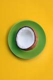Ανοικτή καρύδα σε ένα πράσινο πιάτο ενάντια στην κίτρινη σκιά υποβάθρου Στοκ εικόνα με δικαίωμα ελεύθερης χρήσης