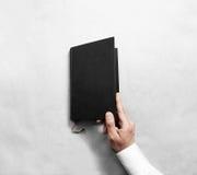 Ανοικτή κενή μαύρη χλεύη κάλυψης βιβλίων χεριών επάνω στο πρότυπο Στοκ Φωτογραφίες