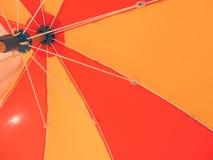 Ανοικτή κόκκινη και πορτοκαλιά ομπρέλα παραλιών από κάτω από Στοκ Εικόνες