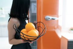 Ανοικτή πόρτα ψυγείων γυναικών στην κουζίνα Πορτοκάλι στη διάθεση στοκ φωτογραφίες με δικαίωμα ελεύθερης χρήσης