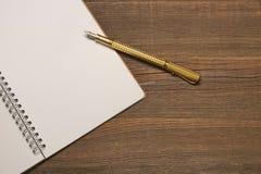 Ανοικτή σπείρα - συνδεδεμένο σημειωματάριο με τις άσπρες σελίδες και τη χρυσή μάνδρα Στοκ Εικόνα