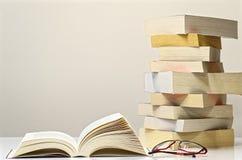Ανοικτοί βιβλίο, γυαλιά και σωρός των βιβλίων στον άσπρο πίνακα στοκ εικόνα