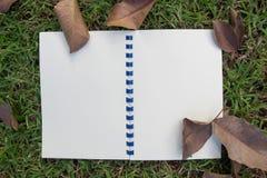 Ανοικτό άσπρο σημειωματάριο στη χλόη στοκ φωτογραφία