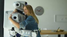 Ανοικτό απασχολημένο κορίτσι που αγκαλιάζει το ρομπότ στενά απόθεμα βίντεο