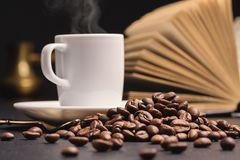 Ανοικτό βιβλίο, άσπρο φλιτζάνι του καφέ, φασόλια καφέ Σκοτεινή ανασκόπηση διάστημα αντιγράφων Στοκ Φωτογραφίες