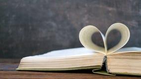Ανοικτό βιβλίο με τη μορφή καρδιών από τη σελίδα εγγράφου στο σκοτεινό ξύλινο πίνακα Λ στοκ εικόνα
