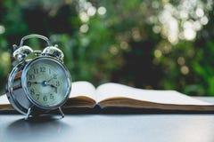 Ανοικτό βιβλίο με το ξυπνητήρι Βιβλίο ανοικτό στον παλαιό ξύλινο πίνακα σε εθνικό Στοκ Φωτογραφίες
