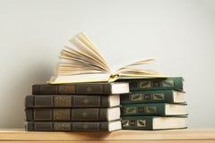 Ανοικτό βιβλίο στο σωρό των βιβλίων στον ξύλινο πίνακα Υπόβαθρο εκπαίδευσης πίσω σχολείο Ελεύθερο διάστημα αντιγράφων Στοκ Εικόνα