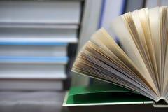 Ανοικτό βιβλίο, σωρός των βιβλίων βιβλίων με σκληρό εξώφυλλο στον πίνακα Τοπ όψη Στοκ Εικόνες