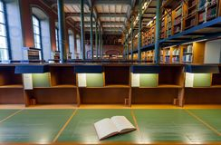 Ανοικτό βιβλίο του αναγνώστη μέσα στην εθνική βιβλιοθήκη της Σουηδίας με το ιστορικό εσωτερικό Στοκ Εικόνα