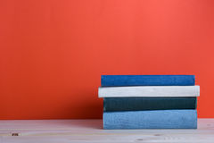 Ανοικτό βιβλίο βιβλίων με σκληρό εξώφυλλο στον ξύλινο πίνακα γεφυρών και το κόκκινο υπόβαθρο Στοκ Εικόνες