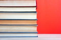 Ανοικτό βιβλίο βιβλίων με σκληρό εξώφυλλο στον ξύλινο πίνακα γεφυρών και το κόκκινο υπόβαθρο Στοκ φωτογραφία με δικαίωμα ελεύθερης χρήσης