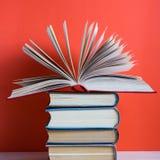 Ανοικτό βιβλίο βιβλίων με σκληρό εξώφυλλο στον ξύλινο πίνακα γεφυρών και το κόκκινο υπόβαθρο Στοκ Φωτογραφία