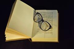 Ανοικτό βιβλίο και οπτικά eyeglasses, μαύρο υπόβαθρο Στοκ φωτογραφίες με δικαίωμα ελεύθερης χρήσης