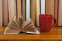 Ανοικτό βιβλίο, κόκκινα ζωηρόχρωμα βιβλία βιβλίων με σκληρό εξώφυλλο φλυτζανιών στον ξύλινο πίνακα πίσω σχολείο Διάστημα αντιγράφ Στοκ Εικόνα