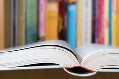 Ανοικτό βιβλίο με μια βιβλιοθήκη στο υπόβαθρο Στοκ Εικόνα