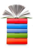 Ανοικτό βιβλίο με τον ελαφρύ ρόλο σελίδων στο σωρό του χρωματισμένου βιβλίου Στοκ Εικόνες