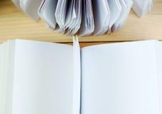 Ανοικτό βιβλίο, σωρός των βιβλίων βιβλίων με σκληρό εξώφυλλο στον ξύλινο πίνακα πίσω σχολείο διάστημα αντιγράφων Στοκ Εικόνα