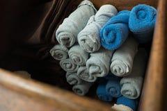Ανοικτό γκρι και μπλε κυλημένη πετσέτα μασάζ SPA στο ξύλινο κιβώτιο Στοκ Εικόνα