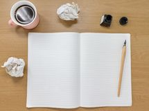 Ανοικτό ευθυγραμμισμένο σημειωματάριο με το φλυτζάνι μελανιού και καφέ σε ένα ξύλινο υπόβαθρο Έννοια συγγραφέων ή καλλιτεχνών με  στοκ φωτογραφία με δικαίωμα ελεύθερης χρήσης