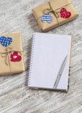 Ανοικτό καθαρό σημειωματάριο, δώρα ημέρας του σπιτικού βαλεντίνου στο έγγραφο του Κραφτ, καρδιές εγγράφου στον άσπρο ξύλινο πίνακ Στοκ φωτογραφίες με δικαίωμα ελεύθερης χρήσης