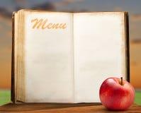 Ανοικτό κενό εκλεκτής ποιότητας βιβλίο επιλογών με το μήλο Στοκ Φωτογραφίες