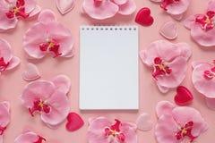 Ανοικτό κενό σημειωματάριο με τα λουλούδια και τις καρδιές ορχιδεών σε μια ρόδινη ΤΣΕ Στοκ εικόνα με δικαίωμα ελεύθερης χρήσης