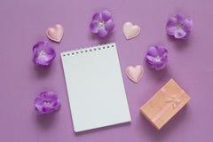 Ανοικτό κενό σημειωματάριο με το κιβώτιο δώρων, τα πορφυρές λουλούδια και τις καρδιές επάνω Στοκ φωτογραφία με δικαίωμα ελεύθερης χρήσης