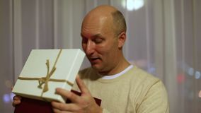 Ανοικτό κιβώτιο δώρων ατόμων Τρέμοντας φω'τα στο πρόσωπό του Ενήλικο καυκάσιο κλείσιμο του ματιού ατόμων και ανοικτό κιβώτιο δώρω απόθεμα βίντεο