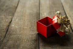 Ανοικτό κόκκινο κιβώτιο δώρων στο ξύλινο γραφείο με το διάστημα αντιγράφων για placeholder κειμένων Στοκ Εικόνες
