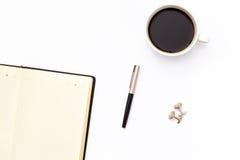 Ανοικτό μαύρο ημερολόγιο με τη μάνδρα και το φλυτζάνι του μαύρου καφέ σε ένα άσπρο υπόβαθρο στοκ φωτογραφία