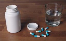 Ανοικτό μπουκάλι χαπιών με τις μπλε κάψες εκτός από ένα νερό glas Στοκ φωτογραφία με δικαίωμα ελεύθερης χρήσης