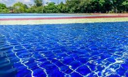 Ανοικτό μπλε, κόκκινο, κίτρινο και μπλε ριγωτό πάτωμα μωσαϊκών της πηγής που καλύπτεται με το σαφές νερό στο υπόβαθρο των blury δ Στοκ Φωτογραφία