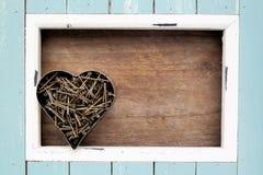 Ανοικτό μπλε πλαίσιο και οξυδωμένα καρφιά, σε μια μορφή καρδιών Στοκ Εικόνα
