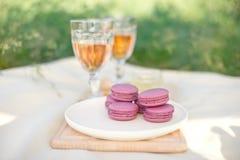 Ανοικτό ροζ και φούξια ρόδινα γαλλικά macaroons ή macaroons με goblets γυαλιού του ρόδινου κρασιού σε ένα στρογγυλό άσπρο πιάτο σ στοκ φωτογραφία με δικαίωμα ελεύθερης χρήσης